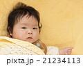 黄色いシーツとおくるみにくるまれた赤ちゃん 21234113