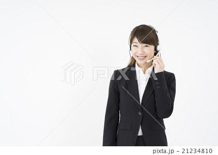 オペレーター:ヘッドセットのマイクを片手に優しく微笑むスーツを着た若く可愛いサポートセンターの女性21234810