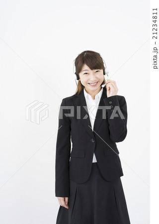 オペレーター:ヘッドセットのマイクを片手に優しく微笑むスーツを着た若く可愛いコールセンターの女性縦 21234811