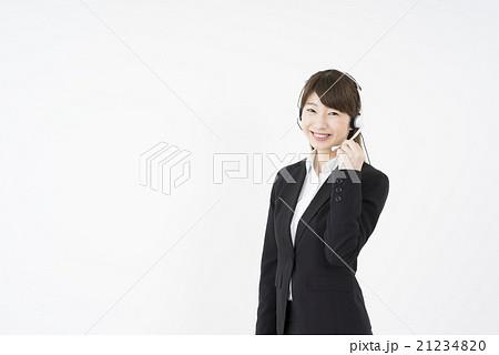 オペレーター:ヘッドセットのマイクを片手に優しく微笑むスーツを着た若く可愛いサポートセンターの女性 21234820