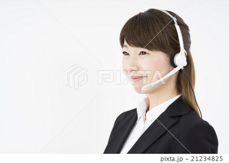 オペレーター:ヘッドセットを付け優しく微笑むスーツを着た若く可愛いサポートセンターの女性横顔ホームページの問い合わせに最適21234825