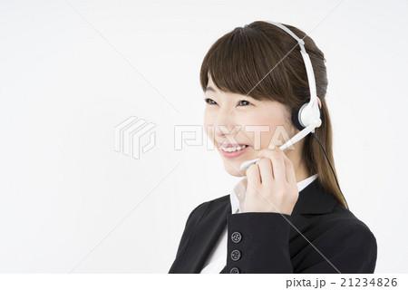 オペレーター:ヘッドセットのマイクを片手に優しく微笑むスーツを着た若く可愛いサポートセンターの女性21234826