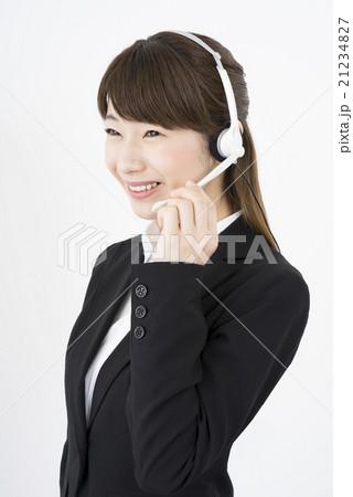 オペレーター:ヘッドセットのマイクを片手に優しく微笑むスーツを着た若く可愛いサポートセンターの女性縦画面構図21234827