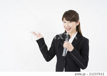 プレゼンテーター:マイクを持ち優しく微笑むスーツを着た若く美人で可愛い女性イベントコンパニオンこちら21237012