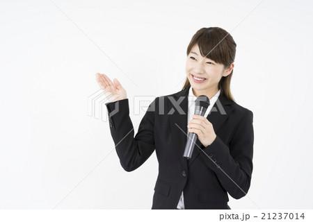 セミナー:マイクを持ち優しく微笑むスーツを着た若く美人で可愛い女性社員、笑顔で会社説明会学生を案内中 21237014