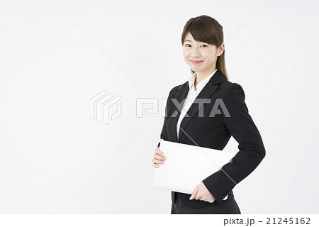 ノートパソコンを片手に持ち優しく微笑む若く美人で可愛いスーツ姿の女性モバイルキャリアウーマンノマド21245162