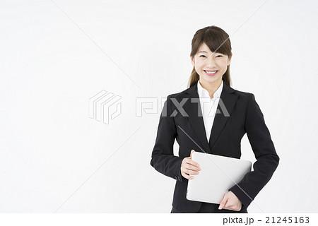 ノートパソコンを片手に持ち優しく微笑む若く美人で可愛いスーツ姿の女性モバイルキャリアウーマンノマド 21245163