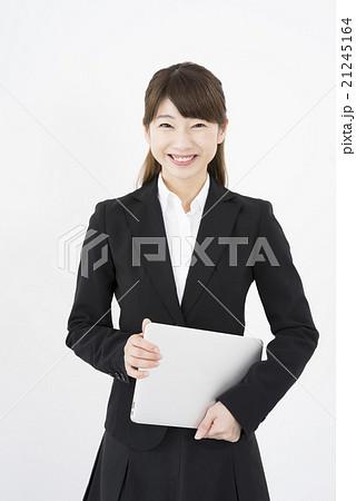 ノートパソコンを片手に持ち優しく微笑む若く美人で可愛いスーツ姿の女性モバイルキャリアウーマン縦画面 21245164