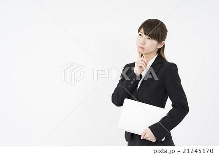 ノートパソコンを片手にデスクワークが苦手で悩む若く美人で可愛いスーツ姿の女性新入社員モバイルノマド21245170