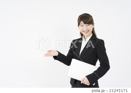 ノートパソコンを片手に提案しながら優しく微笑む若く美人で可愛いスーツ姿の女性モバイルキャリアウーマン21245171