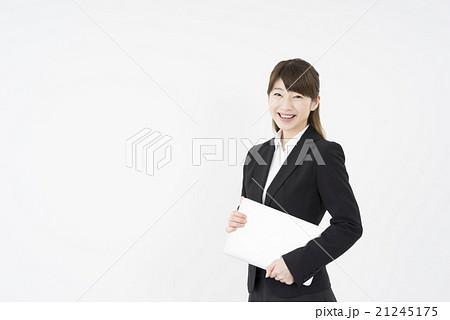 ノートパソコンを片手に持ち優しく微笑む若く美人で可愛いスーツ姿の女性モバイルキャリアウーマンノマド21245175
