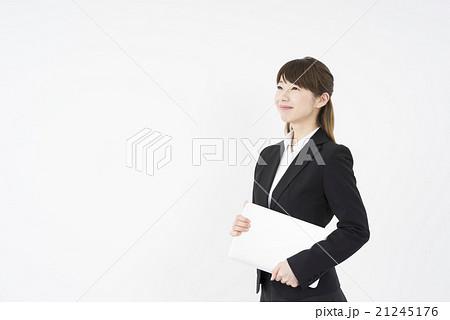 ノートパソコンを片手に未来を見つめ優しく微笑む若く美人で可愛いスーツ姿の女性モバイルキャリアウーマン 21245176