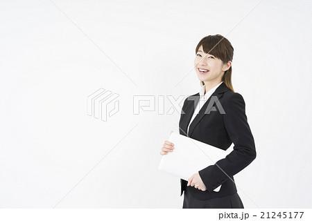 ノートパソコンを片手に持ち優しく微笑む若く美人で可愛いスーツ姿の女性モバイルキャリアウーマンノマド 21245177