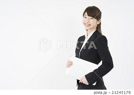 ノートパソコンを片手に持ち優しく微笑む若く美人で可愛いスーツ姿の女性モバイルキャリアウーマンノマド 21245179