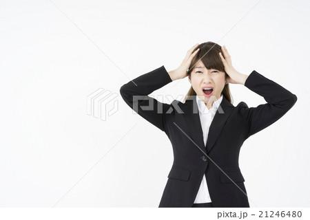 ドタキャンされ両手で頭を抱えパニックになるスーツ姿の女性トラブルでストレス精神的ダメージ悩み困る21246480