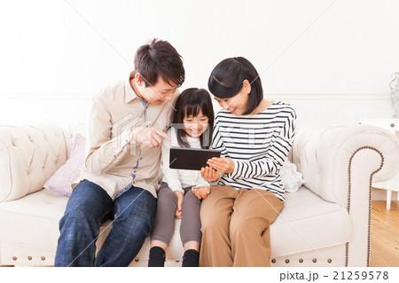 タブレットで動画を楽しむおしゃれな三人家族ポートレート 21259578