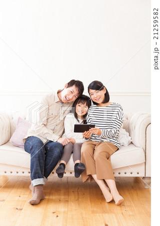 タブレットで動画を楽しむおしゃれな三人家族ポートレート 21259582