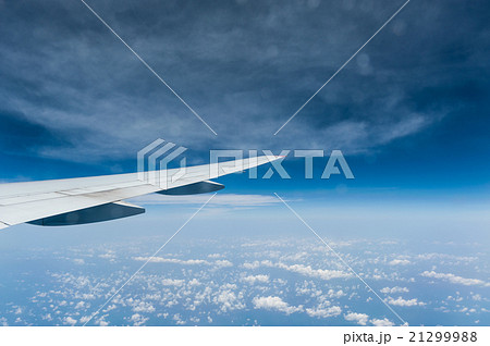 View from airplane window with blue sky and clouds 21299988