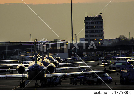 夕暮れ時に空港に停泊している飛行機 21375802