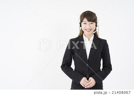 オペレーター:ヘッドセットのマイクを付優しく微笑むスーツを着た若く可愛いサポートセンターの女性 21408067