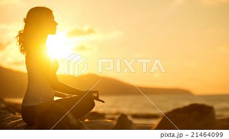 woman meditating in lotus pose on beach at sunset 21464099