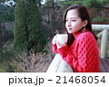 冬の森で温かい飲み物と物思いにふける女の子 21468054
