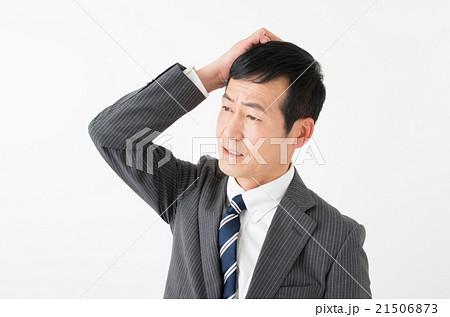 失敗して頭をかくビジネスマンの写真素材