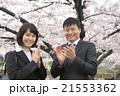 満開の桜を背景に、お祝いの拍手をするフレッシュな会社員 21553362