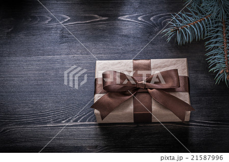 Pine branch wrapped gift box on wooden board 21587996