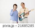 エレキギターを演奏するシニア男性とマイクで歌うシニア女性 21685285