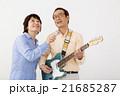 エレキギターを演奏するシニア男性とマイクで歌うシニア女性 21685287
