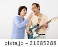 エレキギターを演奏するシニア男性とマイクで歌うシニア女性 21685288