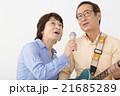 エレキギターを演奏するシニア男性とマイクで歌うシニア女性 21685289