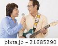 エレキギターを演奏するシニア男性とマイクで歌うシニア女性 21685290