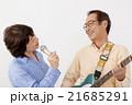 エレキギターを演奏するシニア男性とマイクで歌うシニア女性 21685291