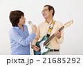 エレキギターを演奏するシニア男性とマイクで歌うシニア女性 21685292