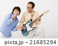 エレキギターを演奏するシニア男性とマイクで歌うシニア女性 21685294