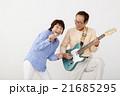 エレキギターを演奏するシニア男性とマイクで歌うシニア女性 21685295