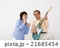 エレキギターを演奏するシニア男性とマイクで歌うシニア女性 21685454