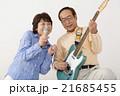 エレキギターを演奏するシニア男性とマイクで歌うシニア女性 21685455