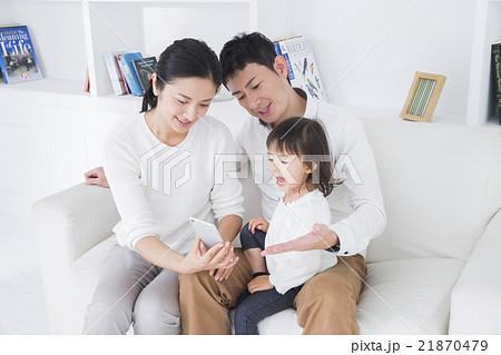 ライフスタイル ソファでスマホを操作する家族3人 21870479