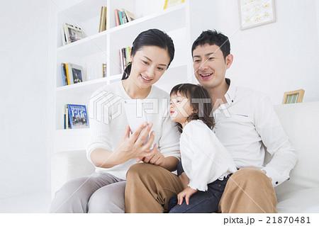 ライフスタイル ソファでスマホを操作する家族3人 21870481