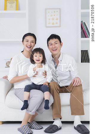 ライフスタイル ソファでスマホを操作する家族3人 21870506