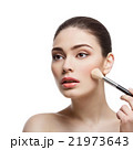 Beautiful girl applying blush with brush 21973643