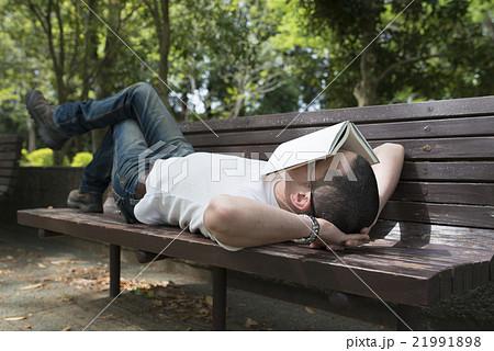 公園のベンチで昼寝をする男性 21991898