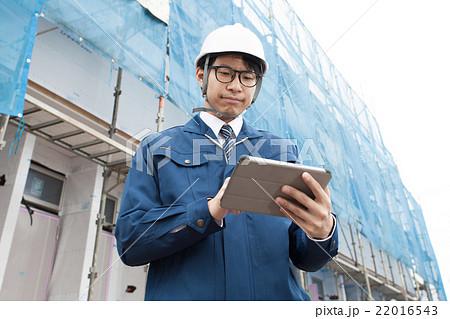 建設現場でタブレットを持って確認している男性 22016543