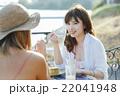 海沿いのカフェでくつろぐ女性 22041948