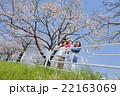 桜の咲く遊歩道で遊ぶ4人家族 22163069