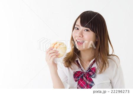 おいしそうにメロンパンを食べる女の子 右向き笑顔 昼食 食事 調理イメージ 女子高校生 22296273