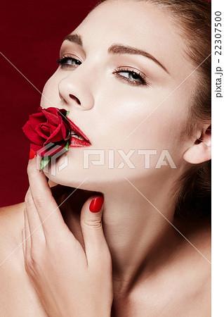 赤いバラと美しい外国人女性の顔のアップ。スキンケア 美容 イメージ 22307500